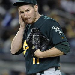 Oakland Athletics starting pitcher Jarrod Parker  reacts after New York Yankees' Nick Swisher scored on a sacrifice fly by Curtis Granderson in the fourth inning of a baseball game on Friday, Sept., 21, 2012, at Yankee Stadium in New York. The Yankees won 2-1 in 10 innings.