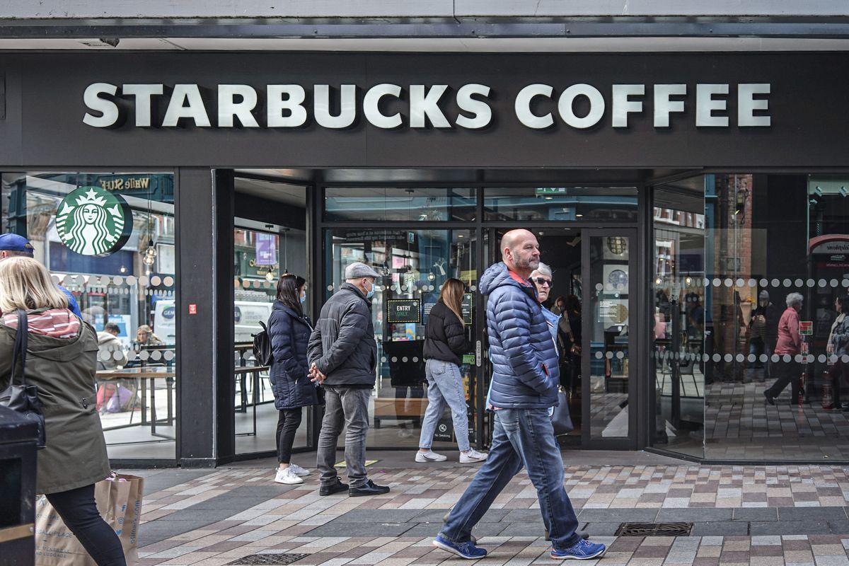 Customers queue to enter Starbucks Coffee Shop...