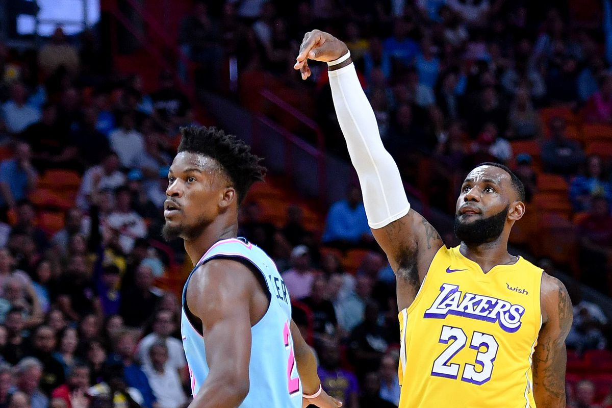 Miami Heat forward Jimmy Butler looks on as Los Angeles Lakers forward LeBron James shoots a three point basket during the first half at American Airlines Arena.