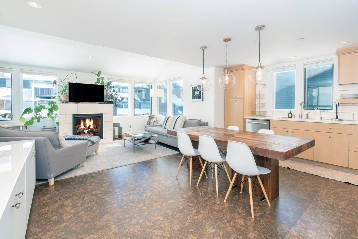 An open floor plan has a small living area with gray couches and a fireplace, cork flooring, and a kitchen with wood island and midcentury modern chairs.