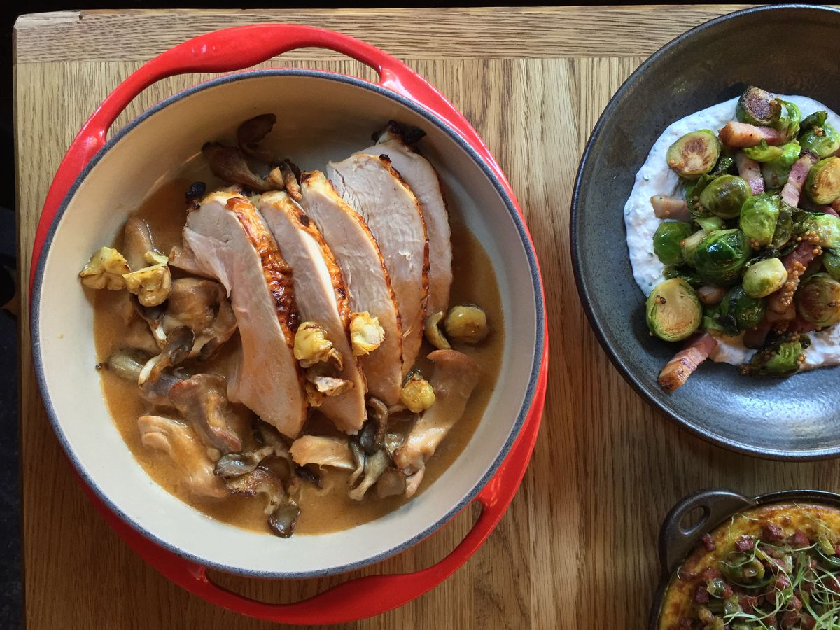 A bowl of sliced turkey meat placed on top of gravy next to a black bowl of brussels sprouts