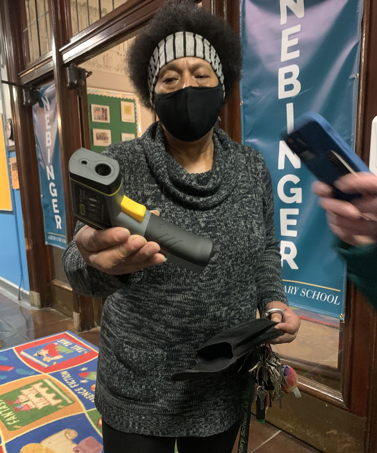 Building engineer Joan Terrell shows off the device used to measure temperatures in classrooms with fans.