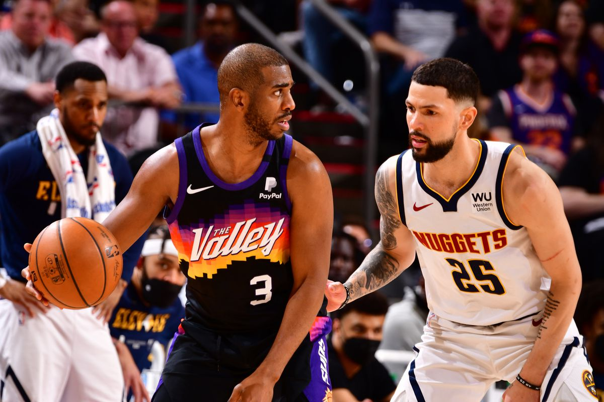 Austin Rivers #25 of the Denver Nuggets plays defense on Chris Paul #3 of the Phoenix Suns during Round 2, Game 1 of the 2021 NBA Playoffs on June 7, 2021 at Phoenix Suns Arena in Phoenix, Arizona.