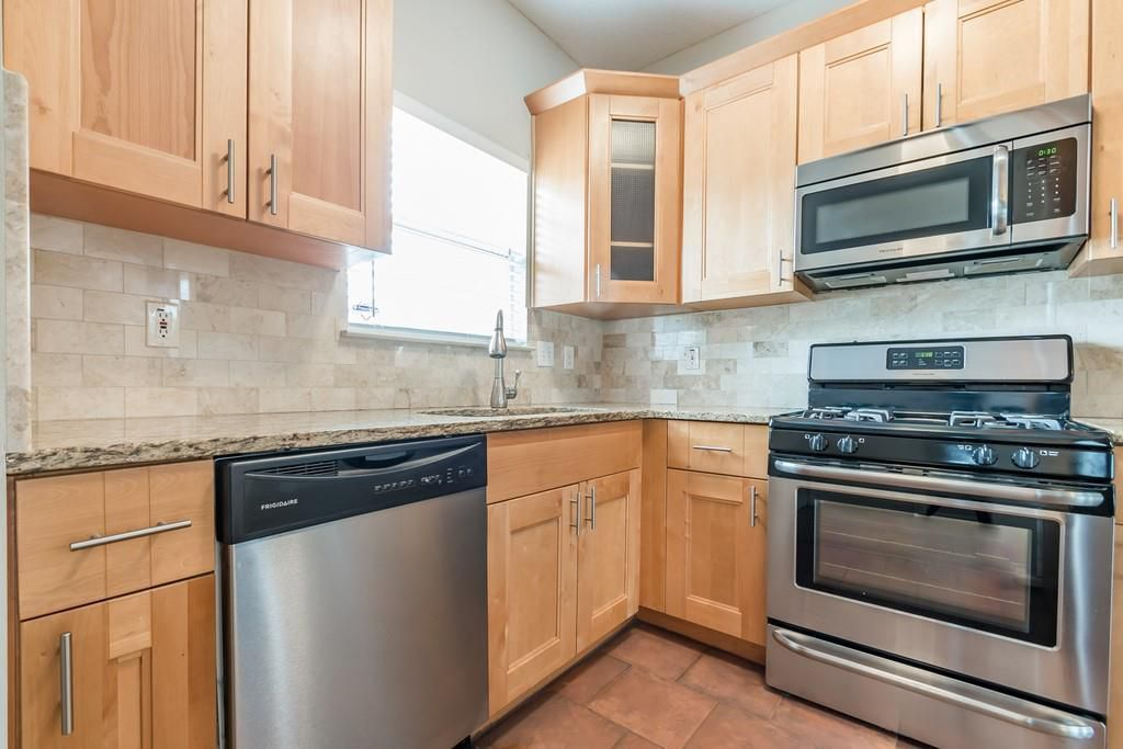 Kitchen with wood cabinets, stainless appliances, and tile backsplash.
