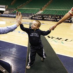 Adam Haggart, left, high-fives Croydon Dyson as the 3-year-old is led off the basketball court by his mother, Mindi Dyson, after auditioning to perform the national anthem at Utah Jazz games this season. Haggart also tried out at EnergySolutions Arena Friday.