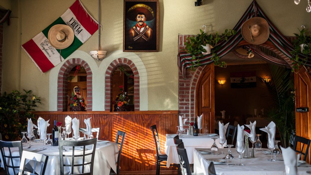 An empty dining room with a flag of Mexico on the wall