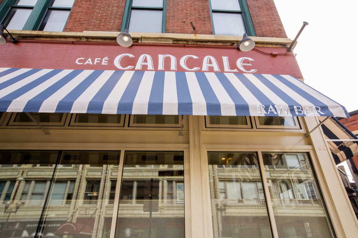 A brick exterior of a restaurant with a striped awning.