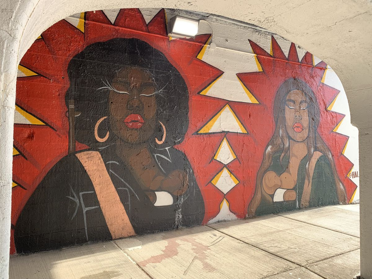 """Pilsen artist Hailey Losselyong says this mural shows """"two very powerful women, one a Black Panther and one a Brown Beret,"""" referring to social justice groups in the Black and Brown communities. """"I wanted to feature them breastfeeding to highlight how women take up a lot of roles, not only raising children but protecting children,"""" and to de-stigmatize what's a """"normal thing."""""""