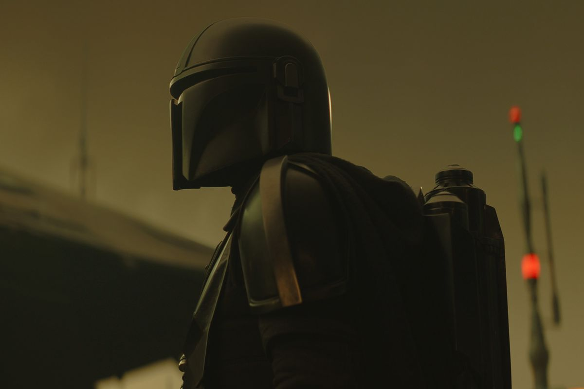 The Mandalorian standing against a yellow brown planet's sky