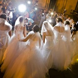 In this Sunday, Aug. 26, 2012 picture, Romanian brides pose for pictures under the Triumph Arch in Bucharest, Romania. The arch, a replica of the Arc de Triomphe in Paris, the French capital, is a rendezvous place for brides on the wedding night for the bride stealing ritual. The ancient Romanian tradition of bride stealing is getting bigger, brasher and an increasingly common sight in the Romanian capital, the region's undisputed party town.