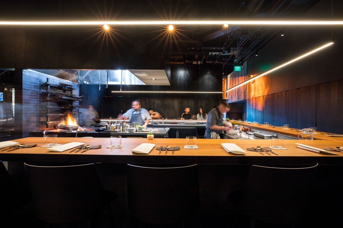 The open kitchen at Gozu, with dramatic open flames visible in the backdrop