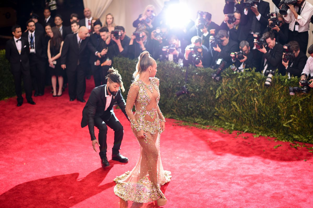 Beyonce wears a sheer gown embellished with crystals. She turns to face the cameras while a man fixes her train.