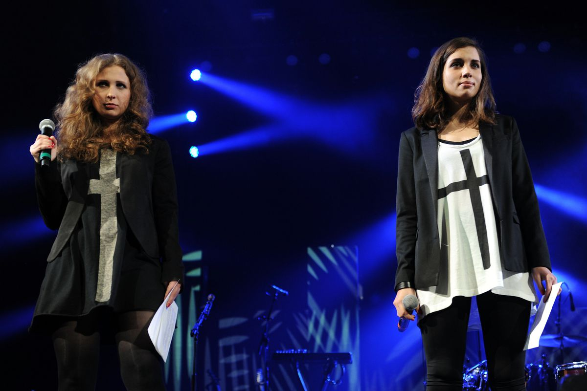 Maria Alyokhina (L) and Nadezhda Tolokonnikova of Russian punk protest group Pussy Riot speak onstage at the Amnesty International Concert