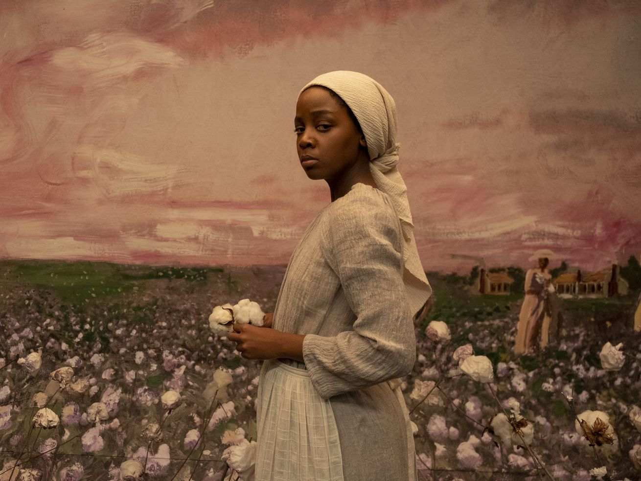 Cora, played by Thuso Mbedu, looks directly at the viewer in front of a mural of a cotton field.