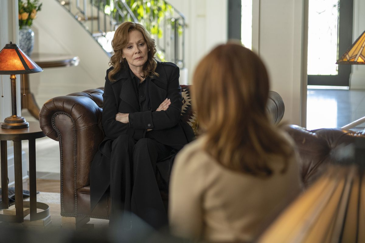 laurie sits in a black jump suit on a leather couch, listening to a red headed woman talk