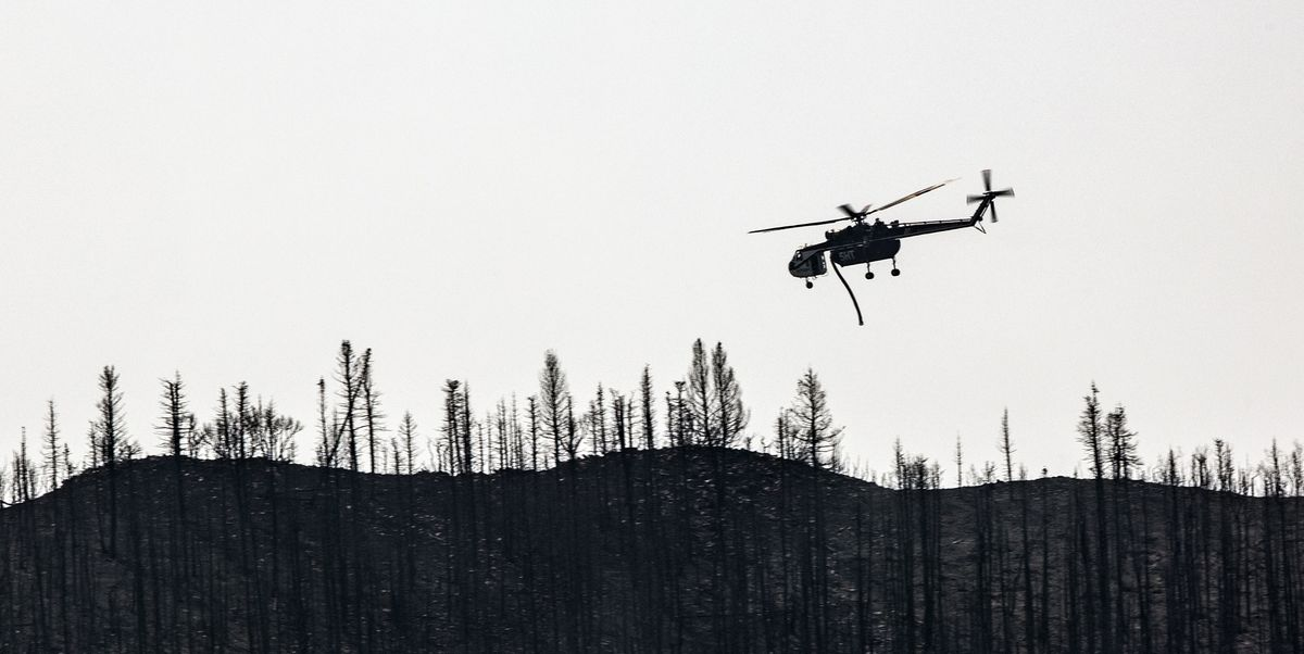 A helicopter flies into drop position as crews fight the Parleys Canyon Fire near Park City on Monday, Aug. 16, 2021.
