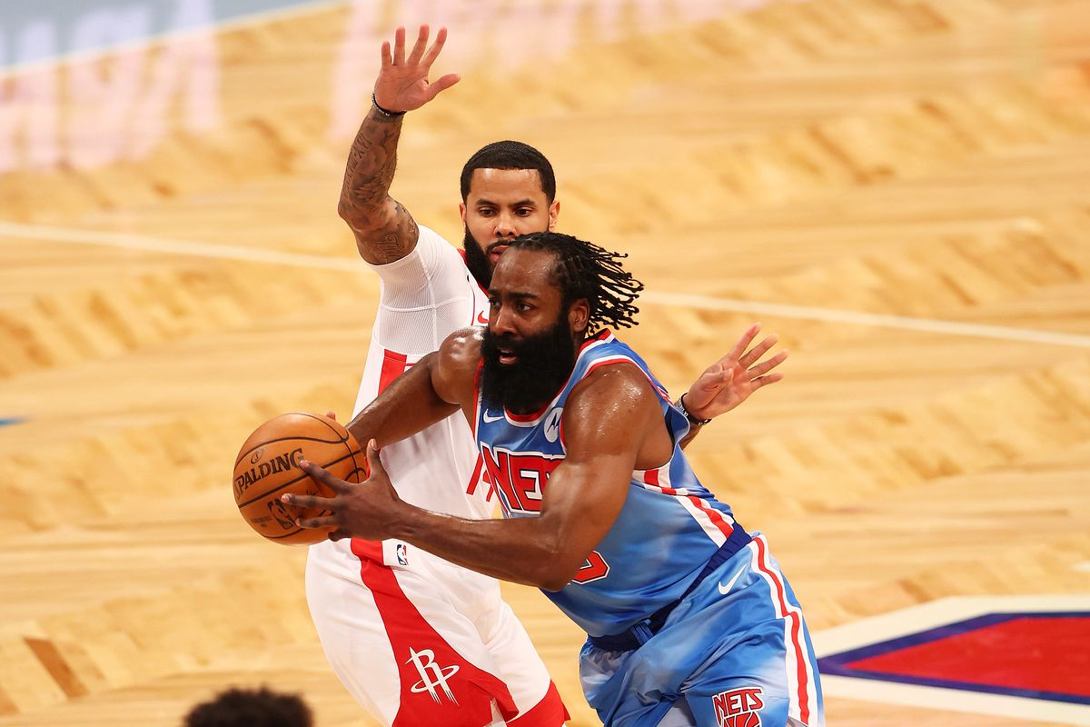 James Harden of the Brooklyn Nets drives to the net against D.J. Augustin of the Houston Rockets at Barclays Center on March 31, 2021 in New York City.