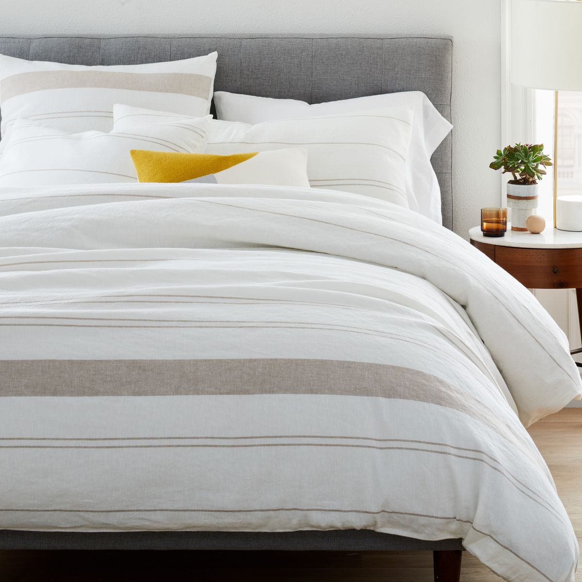 Neutral colored duvet and coverlet on bed.