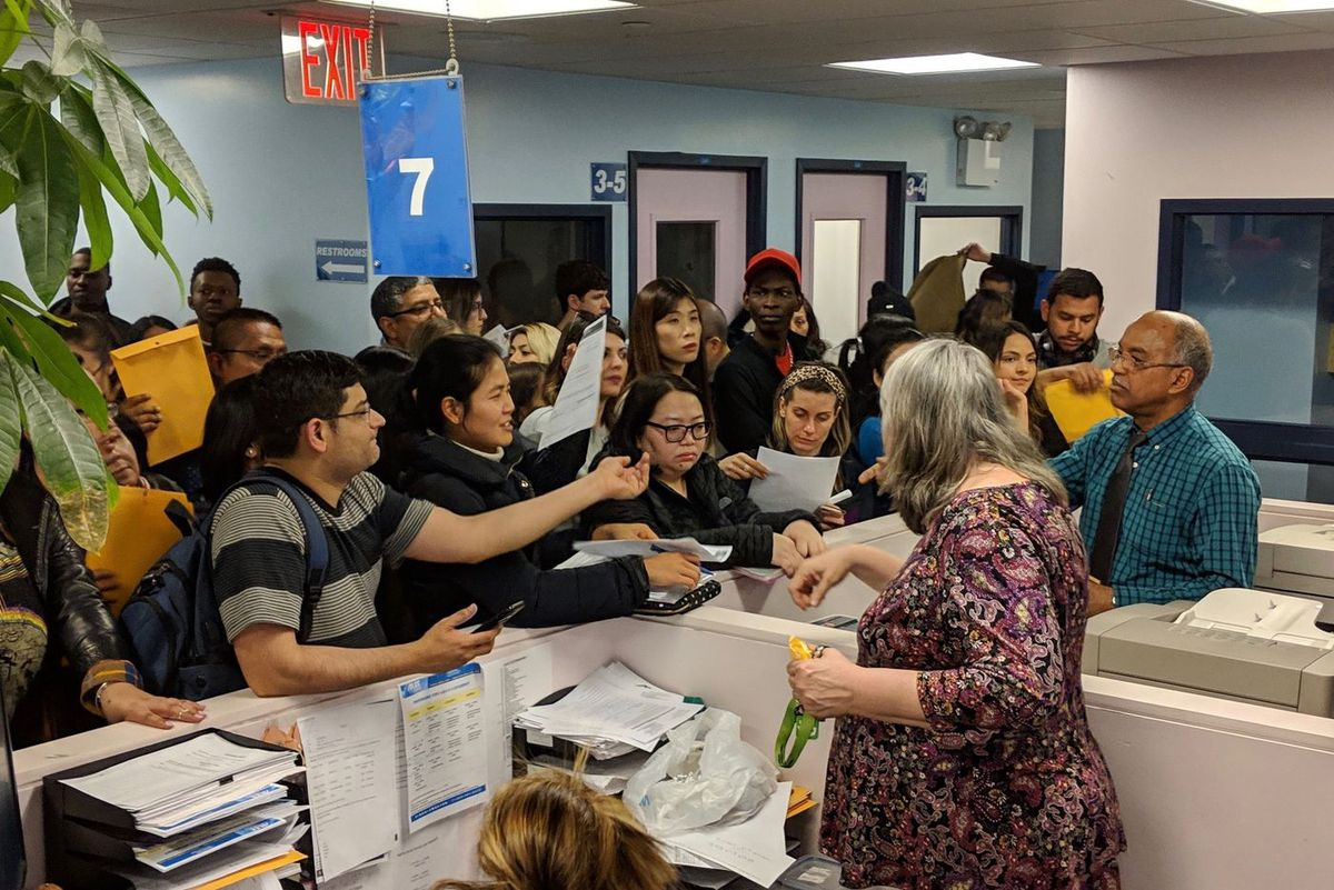 Students line up to receive transfer documents from staff at ALCC on Wednesday, April 3, two days before the English-language school closed.