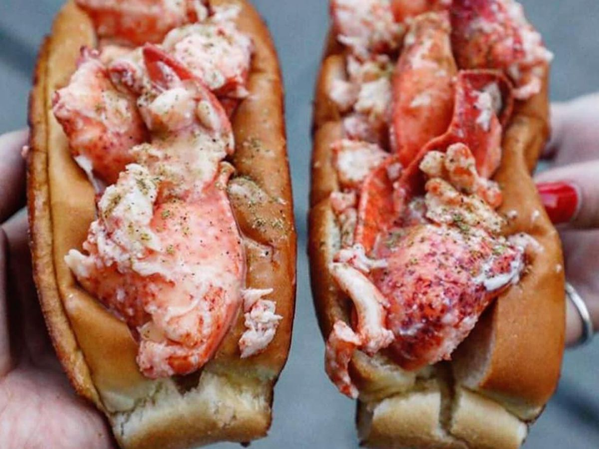 Two lobster rolls held in two hands