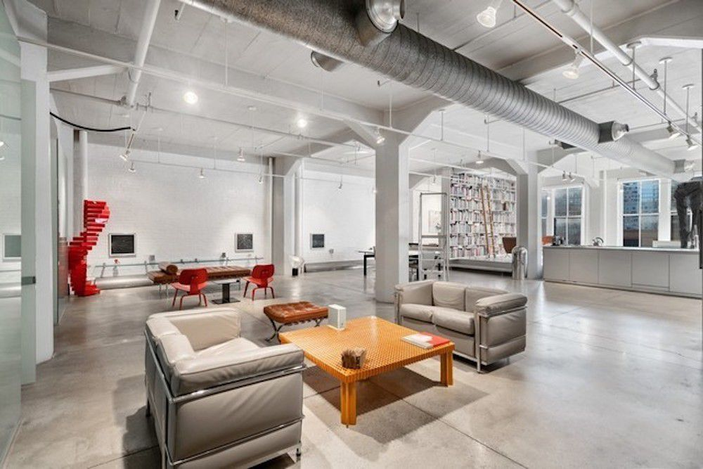 An sprawling industrial loft space with exposed columns, ducts, and concrete floors.
