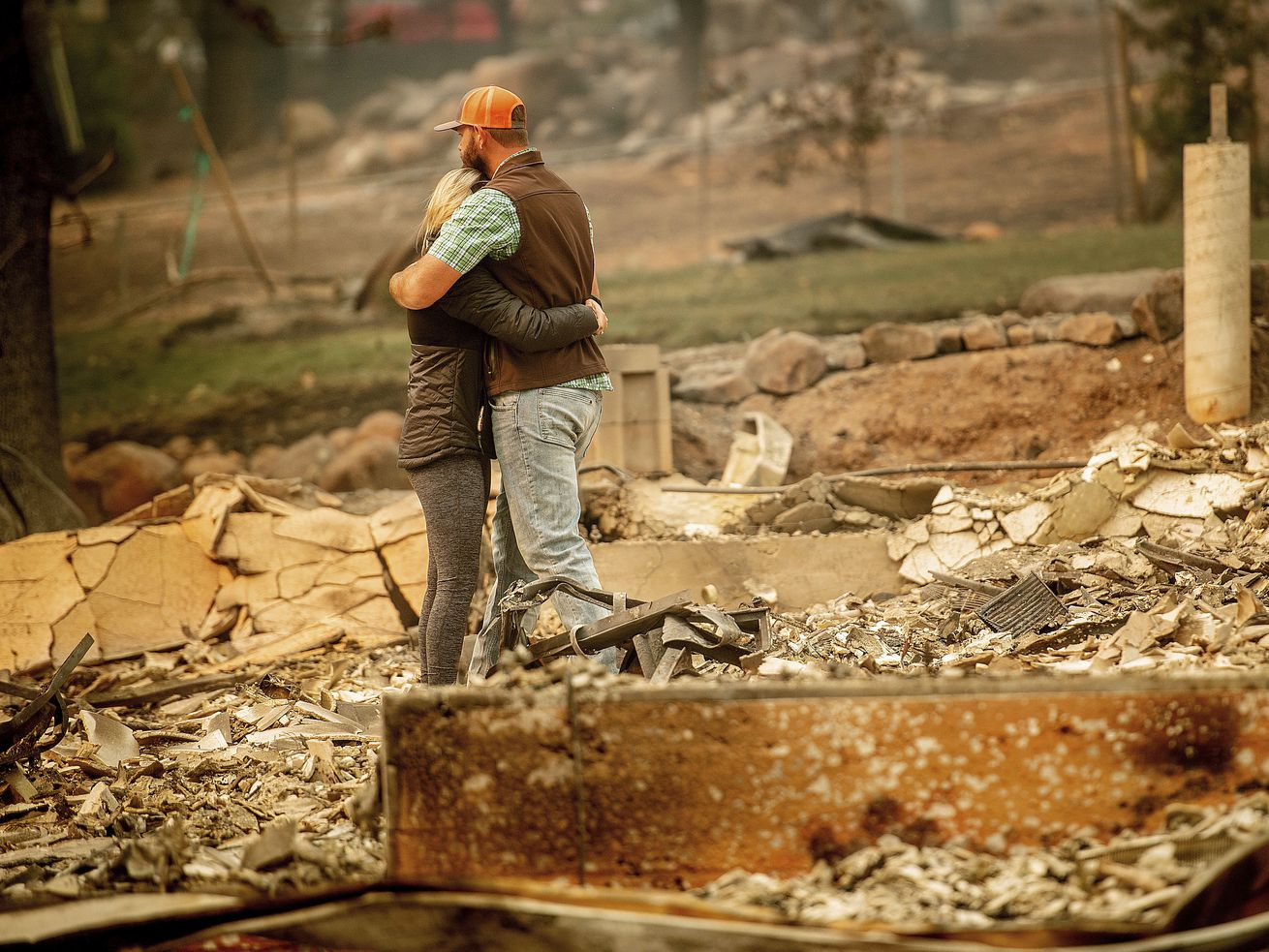 Chris and Nancy Brown embrace while searching through the remains of their home, leveled by the Camp Fire. Nancy Brown escaped from the home with her 2-year-old and three dogs.