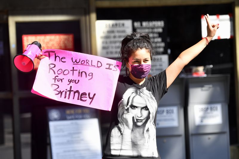 """A masked woman in a Britney Spears T-shirt carries a pink bullhorn and holds a sign saying, """"The world is rooting for you, Britney."""""""