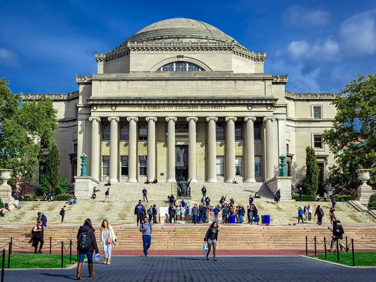 Roman Revival building in the Columbia University Campus with a bronze statue of a woman on its steps.