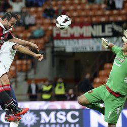 AC Milan forward Giampaolo Pazzini, left, tries to score as Cagliari goalkeeper Michael Agazzi saves the ball during the Serie A soccer match between AC Milan and Cagliari at the San Siro stadium in Milan, Italy, Wednesday, Sept. 26, 2012.