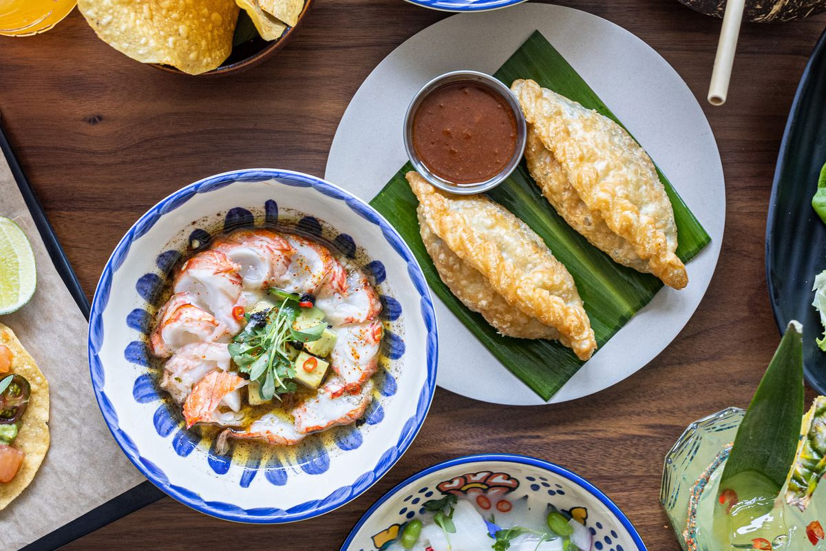 Plates of empanadas and ceviche shot from above. The plates are decorative with blue trim, while the empanadas sit on a banana leaf