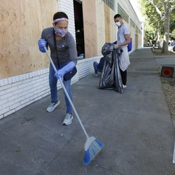 Volunteer Jennifer Kistler-McCoy sweeps up glass from shattered windows at a store Monday, June 1, 2020, that was damaged Sunday in Sacramento, Calif. Nearly two-thirds of the properties in Sacramento's downtown business district were damaged over the weekend following three consecutive days of protests over the killing of George Floyd, a black man who died after being restrained by Minneapolis police officers on May 25.