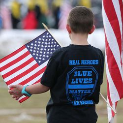 A boy carries a U.S. flag and wears a T-shirt with a special message at the gravesite of Unified police officer Doug Barney at the Orem City Cemetery on Monday, Jan. 25, 2016. Barney was killed in the line of duty on Jan. 17, 2016.