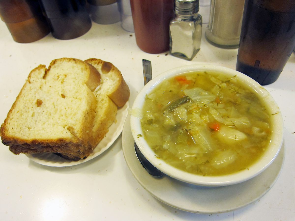 A bowl of cabbage soup speckled with orange carrots and challah bread on the side on a white counter.
