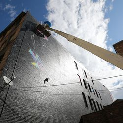 Street artist Vexta works on a five-story tall, 150-foot-long mural in downtown Salt Lake City on Wednesday, Sept. 13, 2017. Utah based 3 Irons commissioned work.