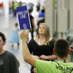 Salt Lake Comic Con volunteer Benjamin Gilbert directs patrons during the convention at the Salt Palace in Salt Lake City Friday, Sept. 5, 2014.