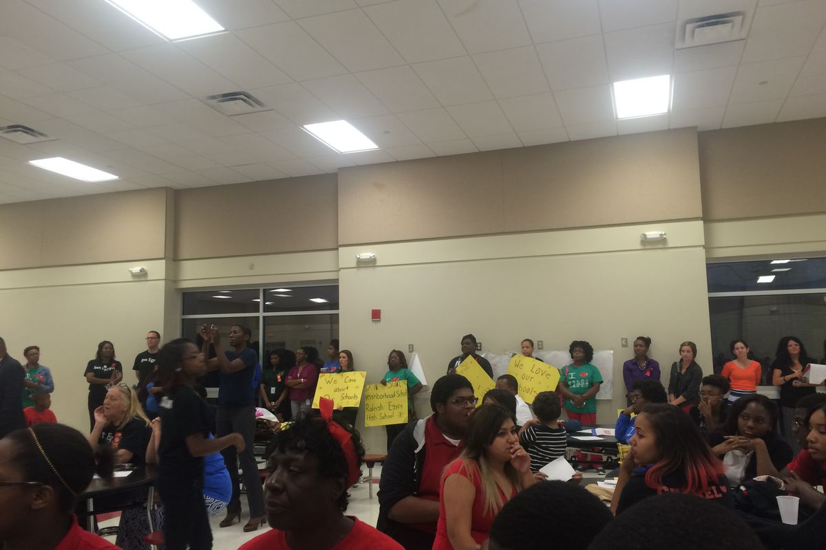 Teachers held signs protesting the ASD takeover during a community meeting at Denver Elementary