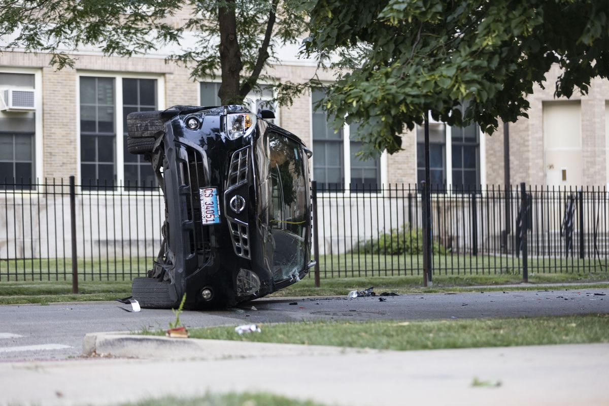 A car on its side at a crime scene at the corner of W Douglas Blvd and S Ridgeway Ave in Lawndale, Wednesday, July 21, 2021. | Anthony Vazquez/Sun-Times