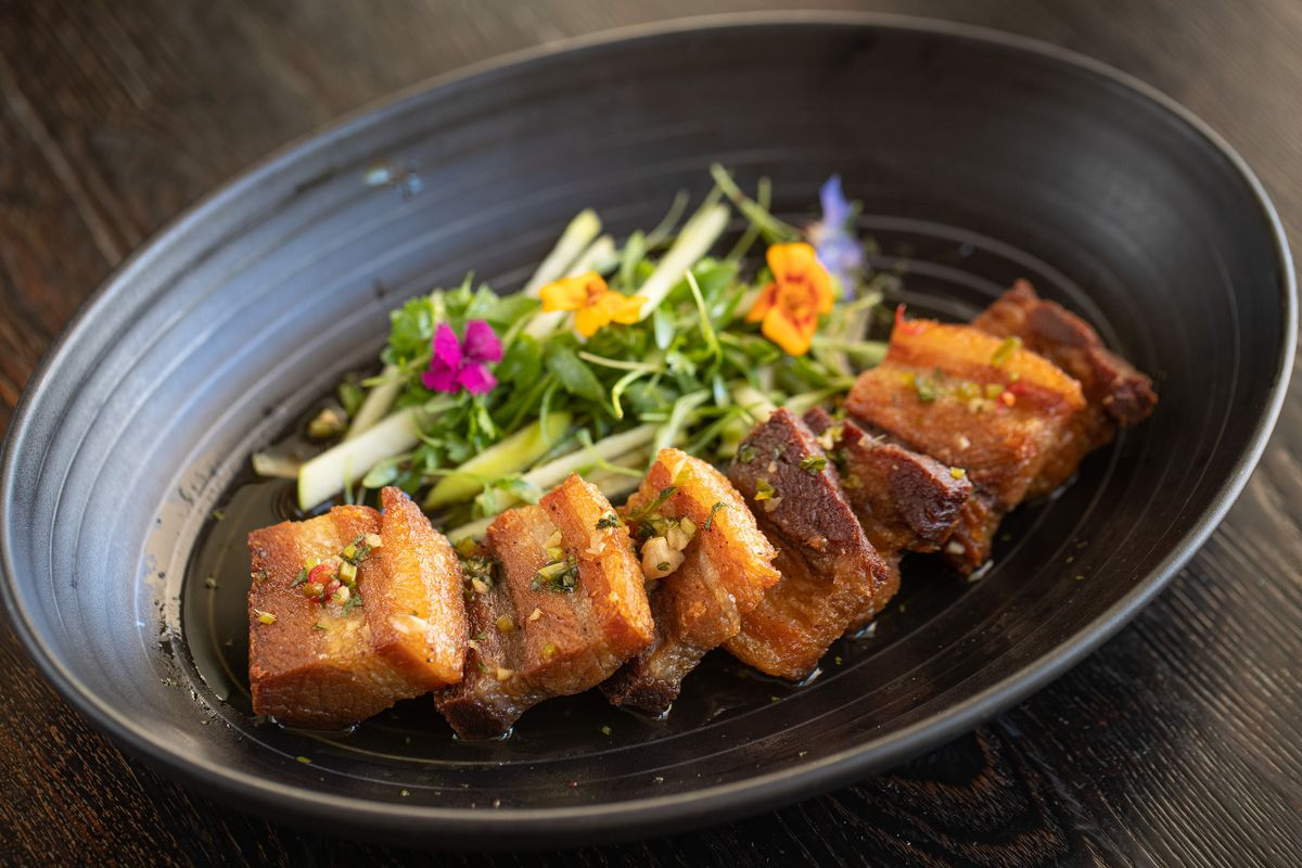 Pork belly dish with apples, herbs, and sauce on a dark plate.
