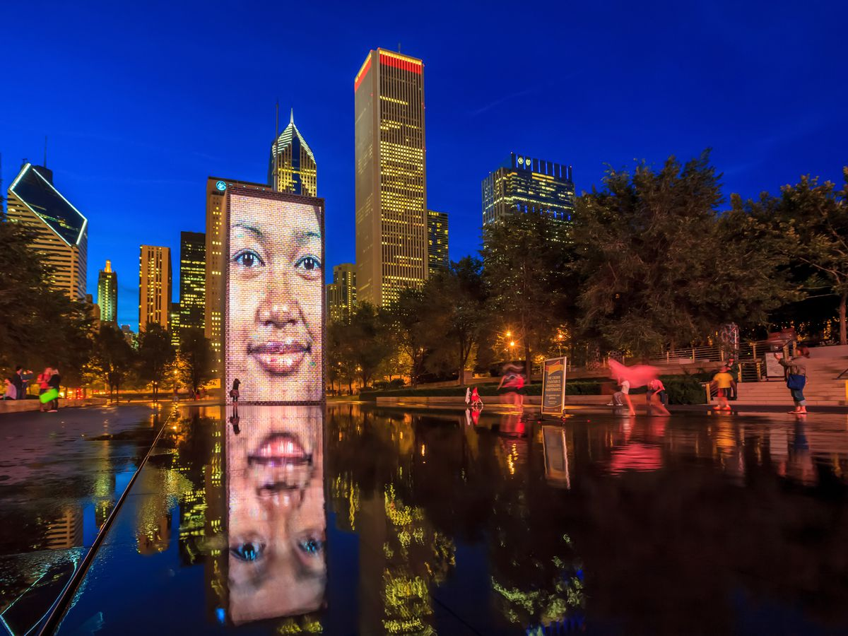 A fountain in Chicago with an LED display that is showing a person's face. The water spouts out of the person's mouth.