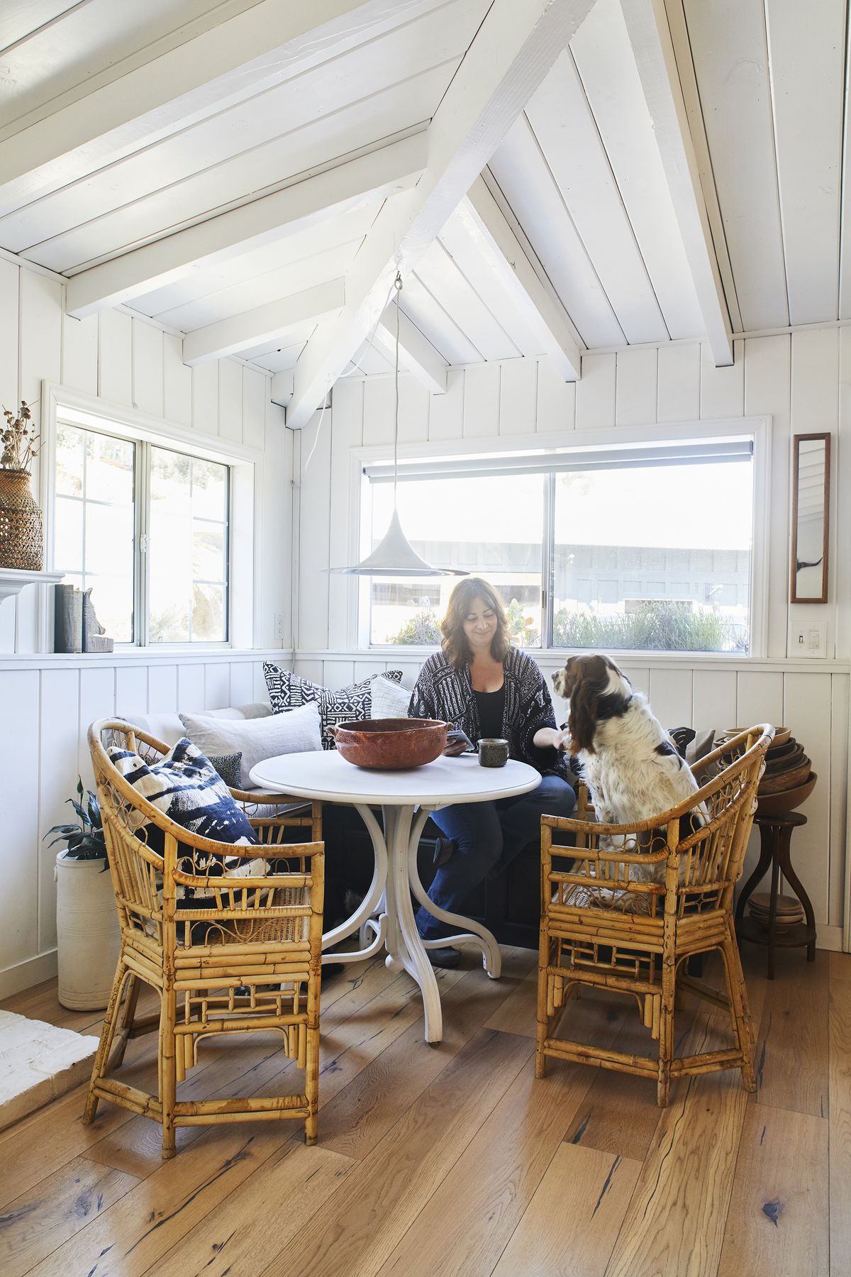 A dining nook has a banquette, wicker chairs, and a table. The paneled walls and ceiling are painted white. Maxcy sits at the table with her brown-and-white dog.