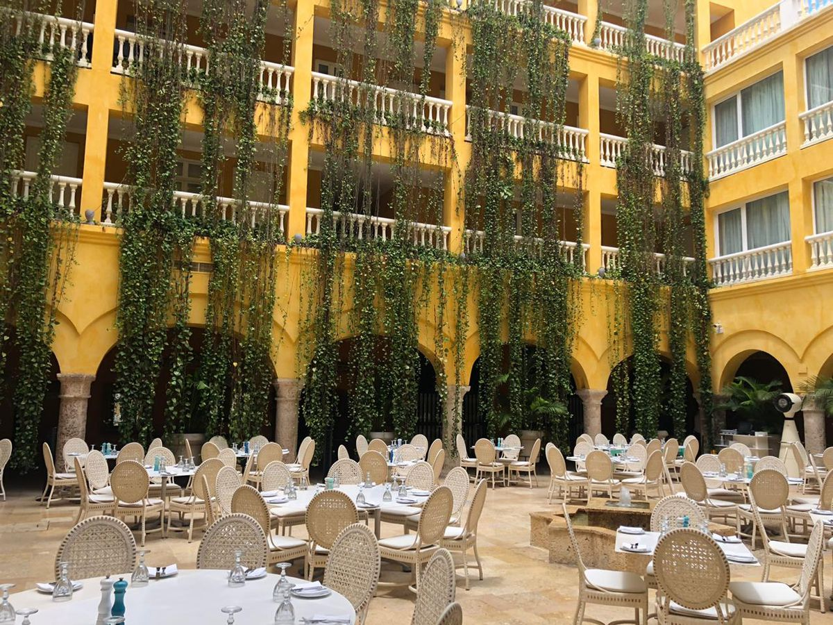 Large patio tables with woven chairs sit in an interior courtyard surrounded by tall hotel buildings draped with hanging plants that run several floors