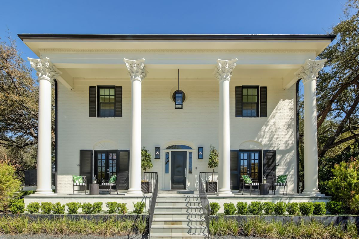 Front of a traditional two-story with big porch and columns in front, white