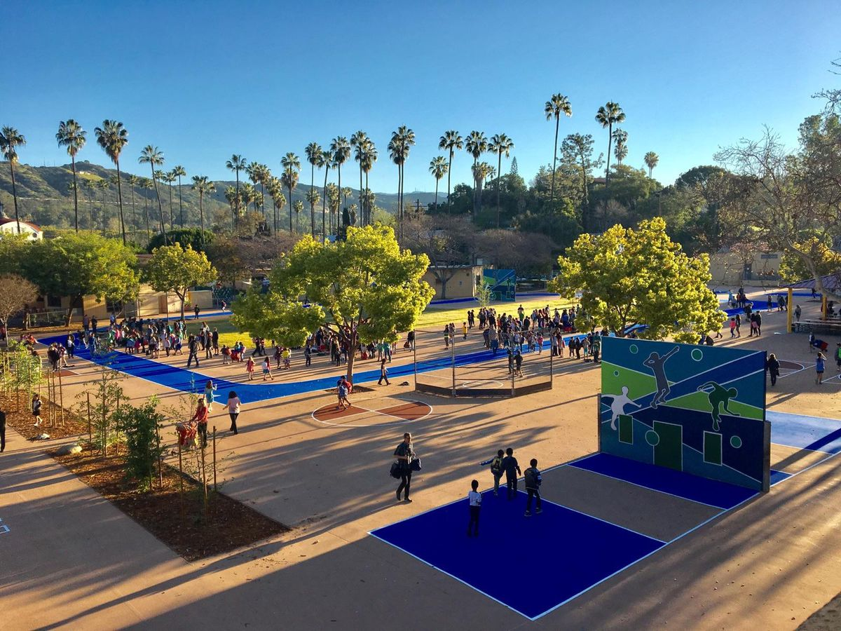 Aerial view of the playground at Eagle Rock Elementary, featuring many trees and blue painted game and play spaces for children.