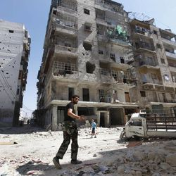 A Frre Syrian Army soldier, walks next of a destroyed building that was attacked by a Syrian government airstrike earlier in the day at al-Shaar neighborhood, in Aleppo city, Syria, Monday Sept. 24, 2012. Most of those fighting the regime of President Bashar Assad are ordinary Syrians and soldiers who have defected, having become fed up with the authoritarian government, analysts say. But increasingly, foreign fighters and those adhering to an extremist Islamist ideology are turning up on the front lines.