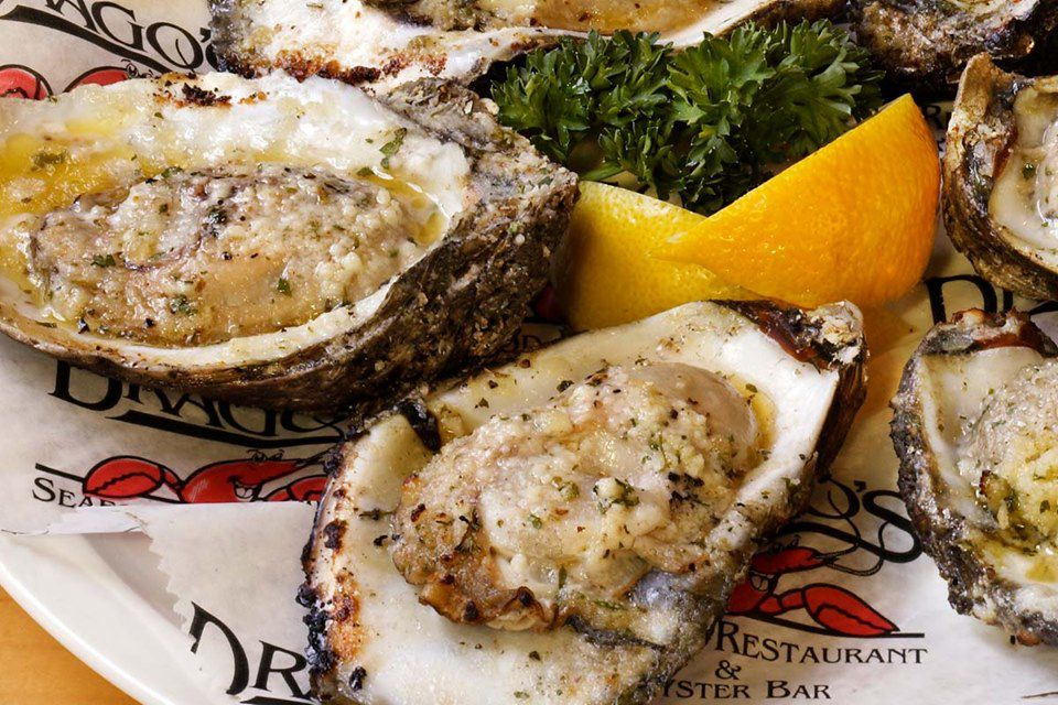 A plate of chargrilled oyster served with lemon wedges and sprigs of parsley.