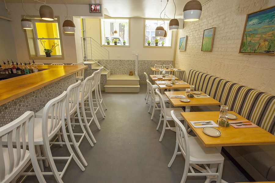 A narrow below-ground restaurant space with rows of two-top tables