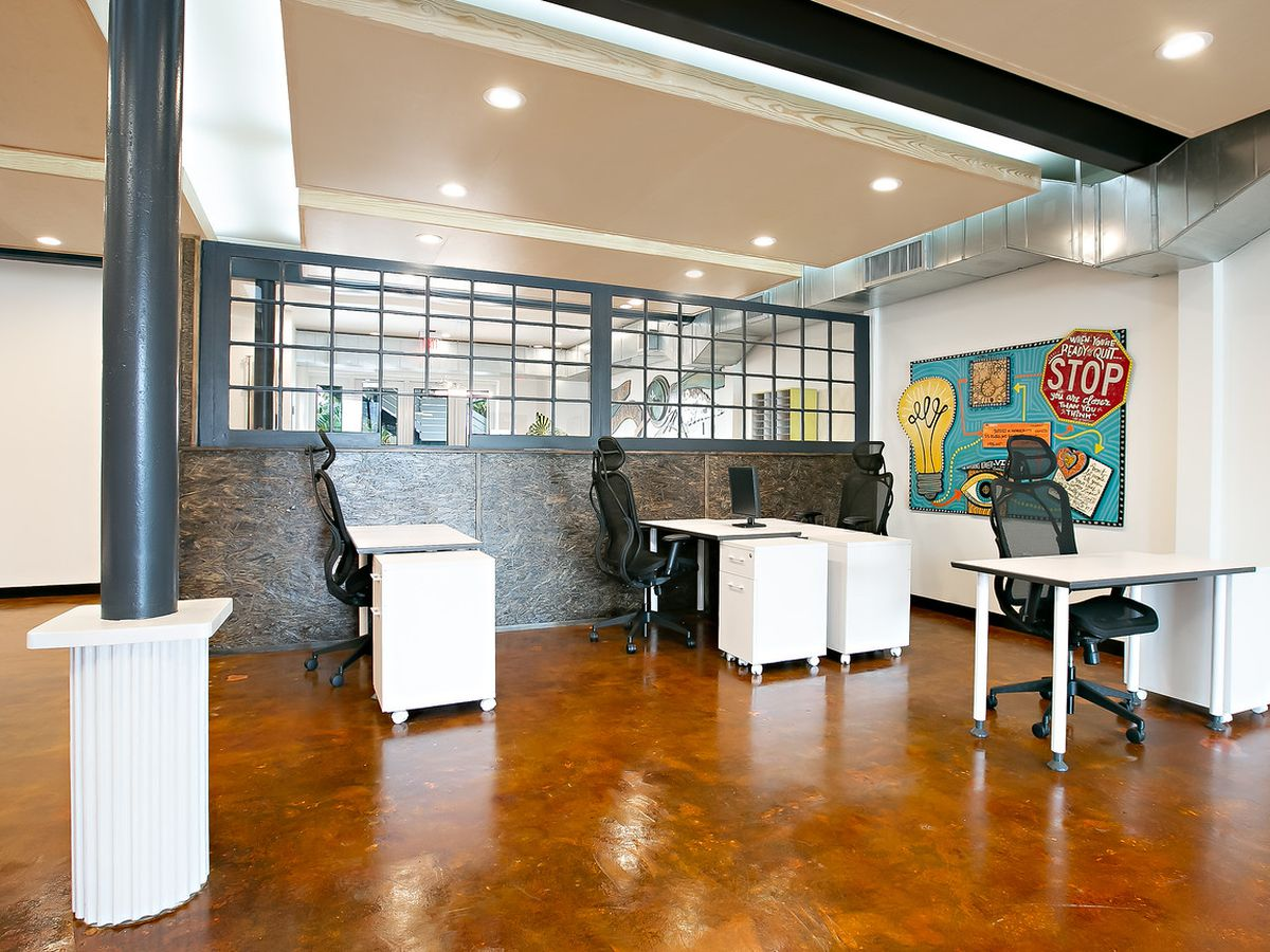 A white office with black columns and a colorful mural is filled with four desks.