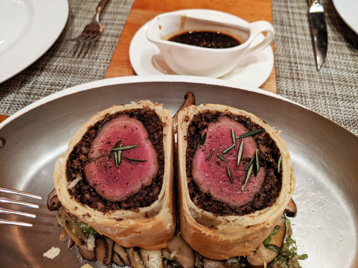 Two cylinders of deer meat with a rare center are wrapped in flaky pastry, with mushrooms underneath.