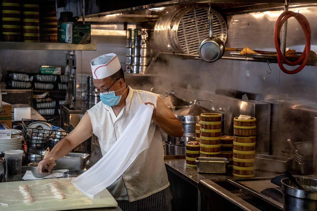 A chef in a face covering is preparing dim sum in a kitchen