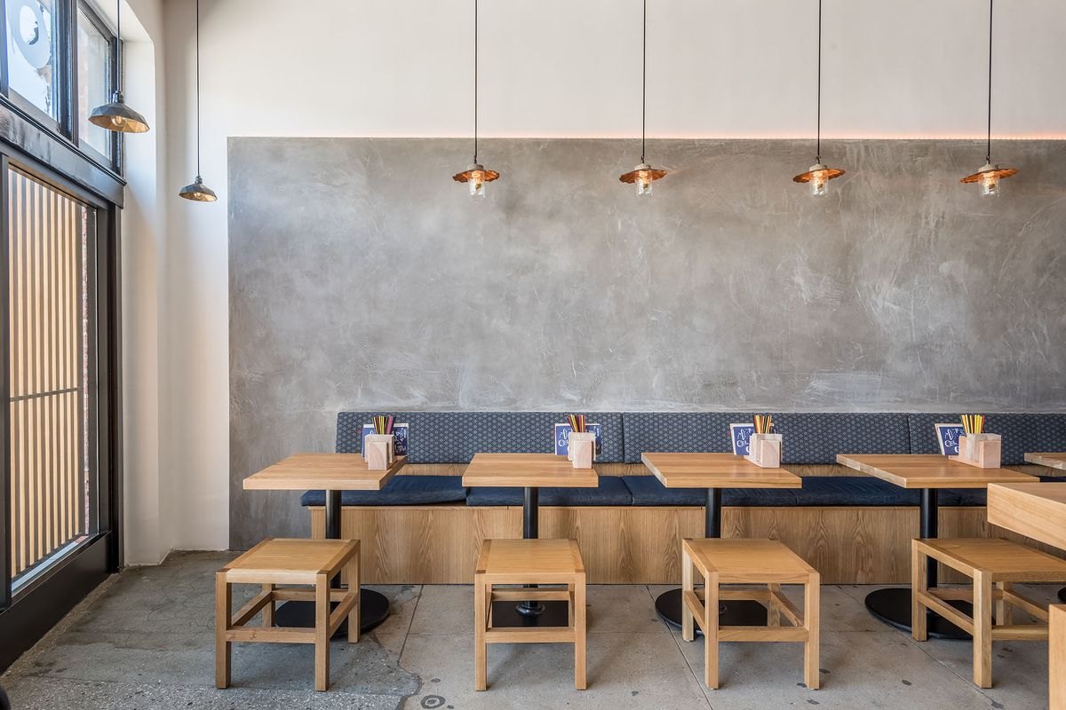 Inside of Ototo restaurant with small wooden stools, small tables, and a sleek concrete wall with hanging lights.